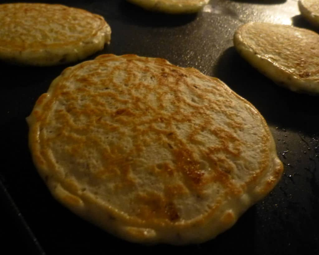 Cottage cheese pancakes nearly finished cooking on the electric griddle.