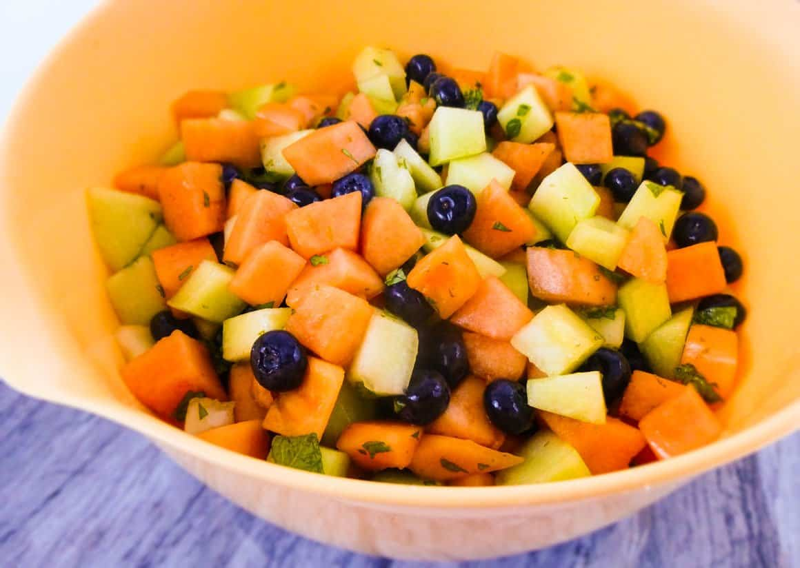 Melon Fruit Salad with Honey Lime Mint Dressing in mixing bowl