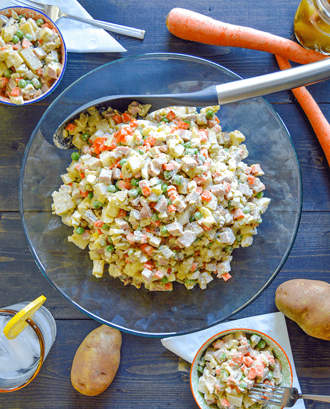 Olivier Russian Potato Salad aka Salat Olivye in a large serving bowl with carrots, potatoes and pickles